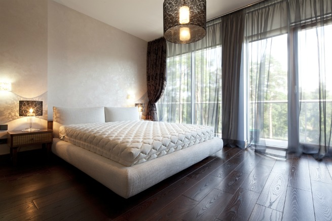 An image of a bed room with a wooden floor