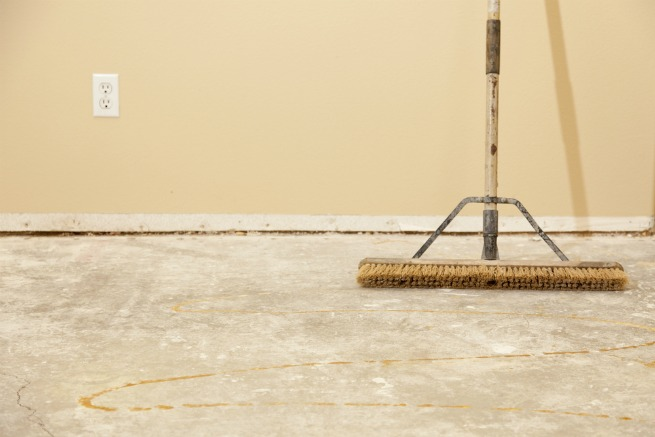 An image of a broom on concrete flooring