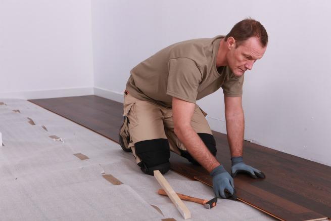 Man installing floor over underlay