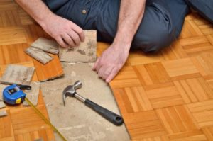 An image of someone removing laminate flooring