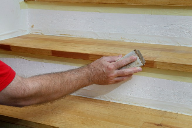 Image of man sanding stairs