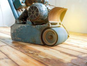 An image of someone sanding wood flooring