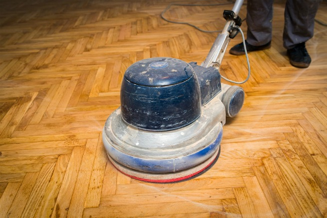 An image showing a sander on a wood floor